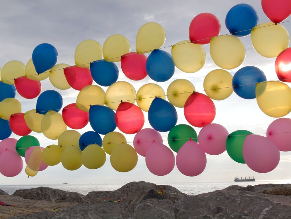 multi colored balloons on brown rock formation near body of water during daytime