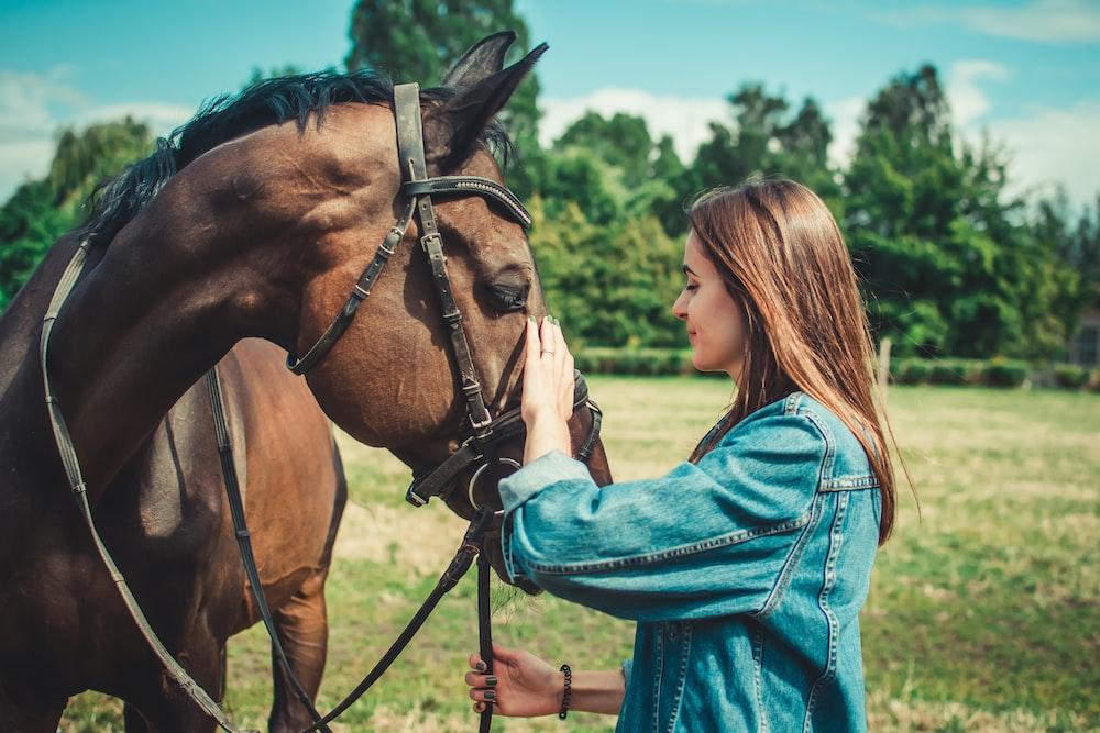 woman in blue denim jacket standing beside brown horse during daytime