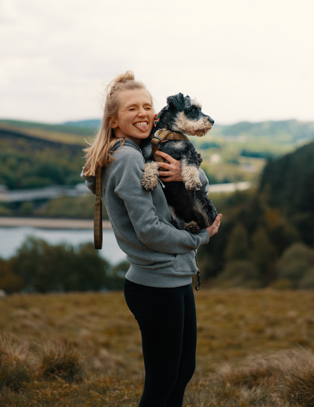 woman in gray jacket carrying black and white short coated small dog