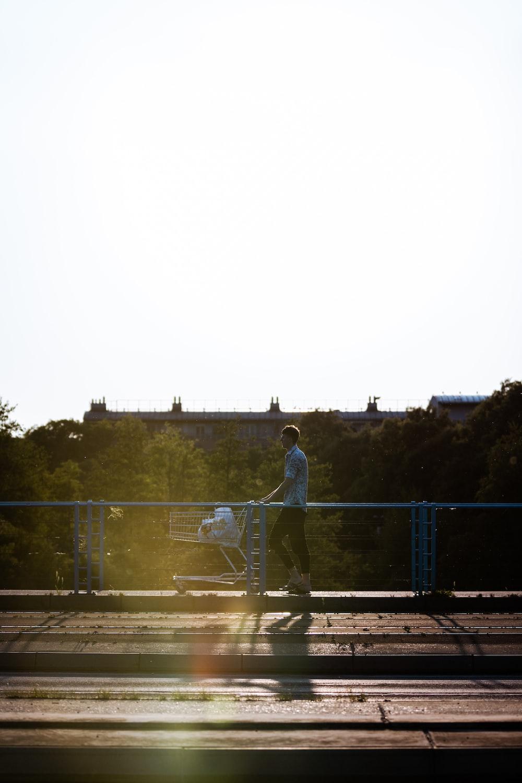man in white shirt standing on bridge during daytime