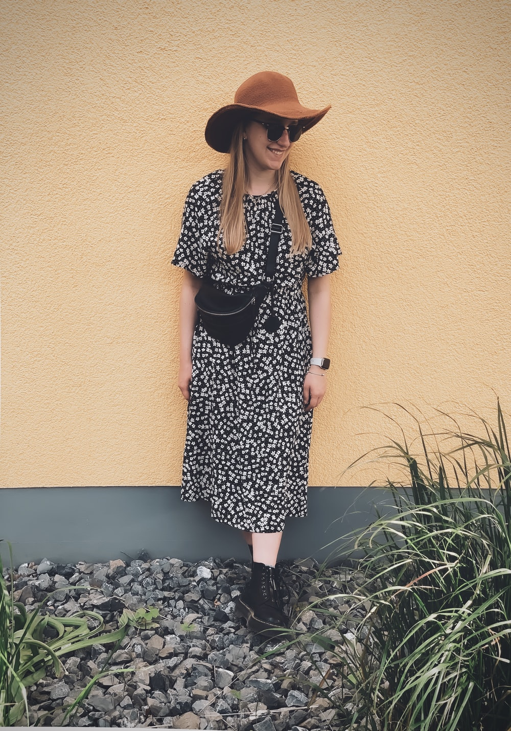 woman in black and white polka dot dress wearing brown sun hat standing beside green plants