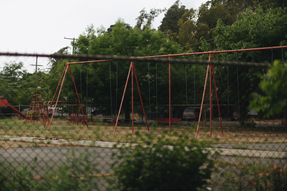 red and black swing near green trees during daytime
