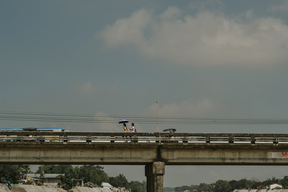 white and blue train on rail under gray sky