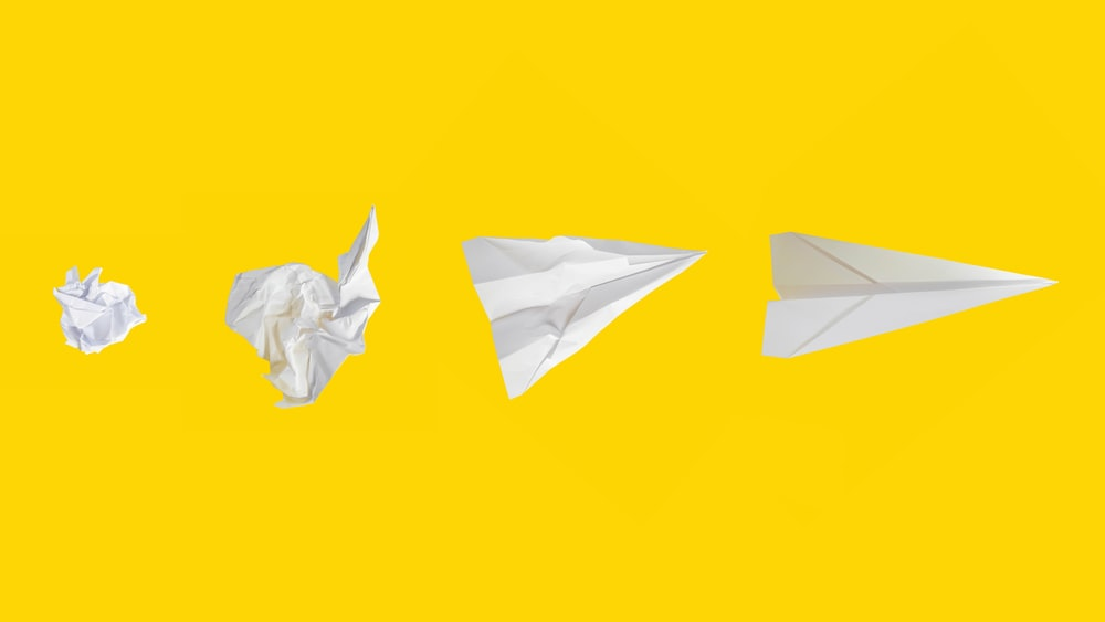 white paper plane on yellow background