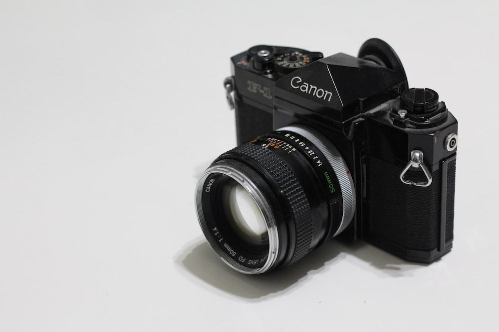 black nikon dslr camera on white surface