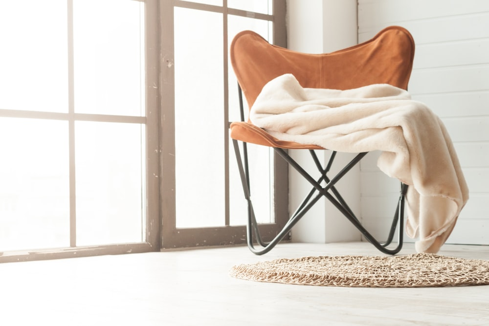 brown wooden chair near white textile on brown wooden floor