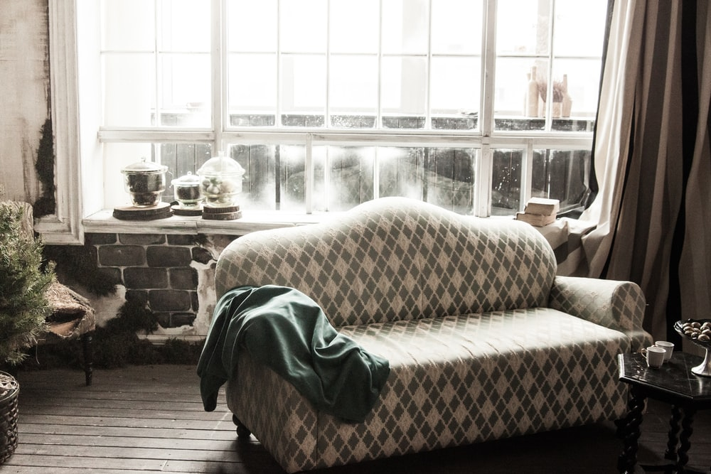 green textile on brown and white sofa
