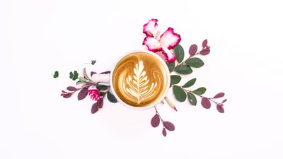 white ceramic cup with brown liquid latte teams background