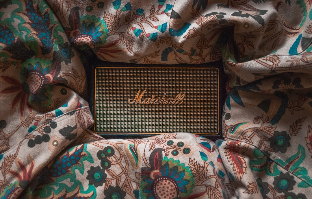 Marshall Kilburn Bluetooth Speakers on a colorful bean bag with floral pattern.