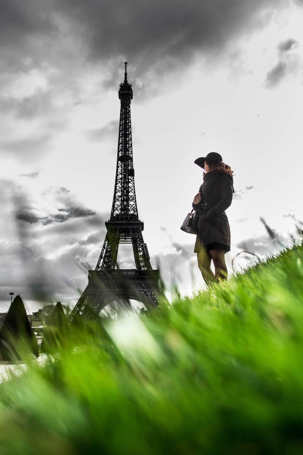 man in black jacket and black hat sitting on green grass near eiffel tower during daytime