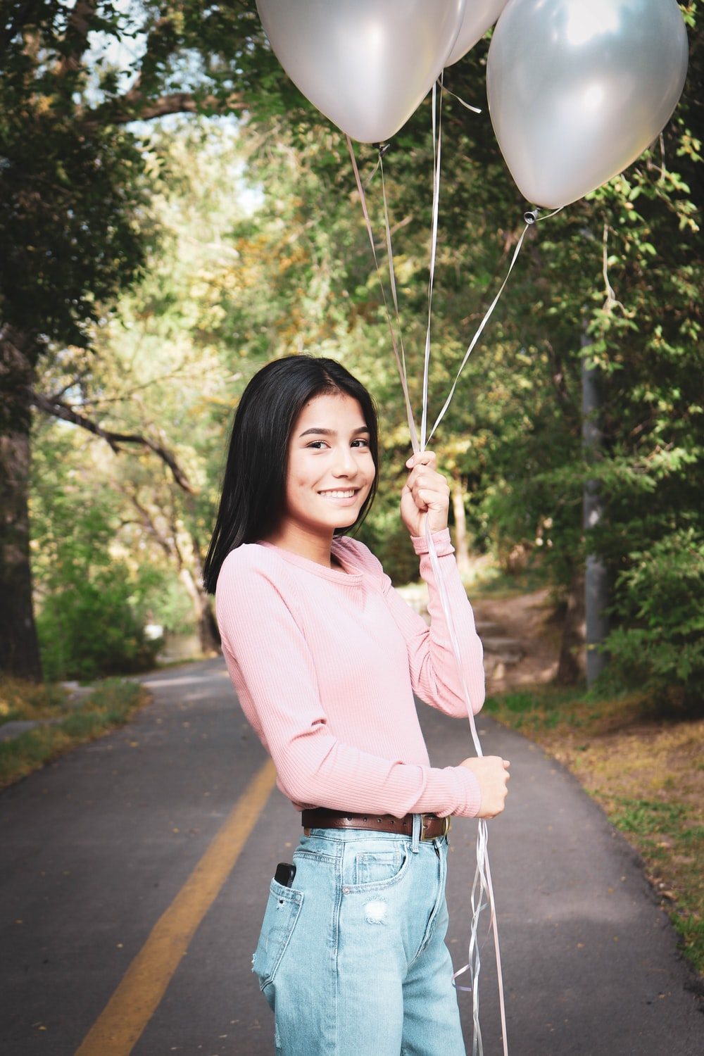 woman in pink long sleeve shirt and blue denim jeans holding white balloons