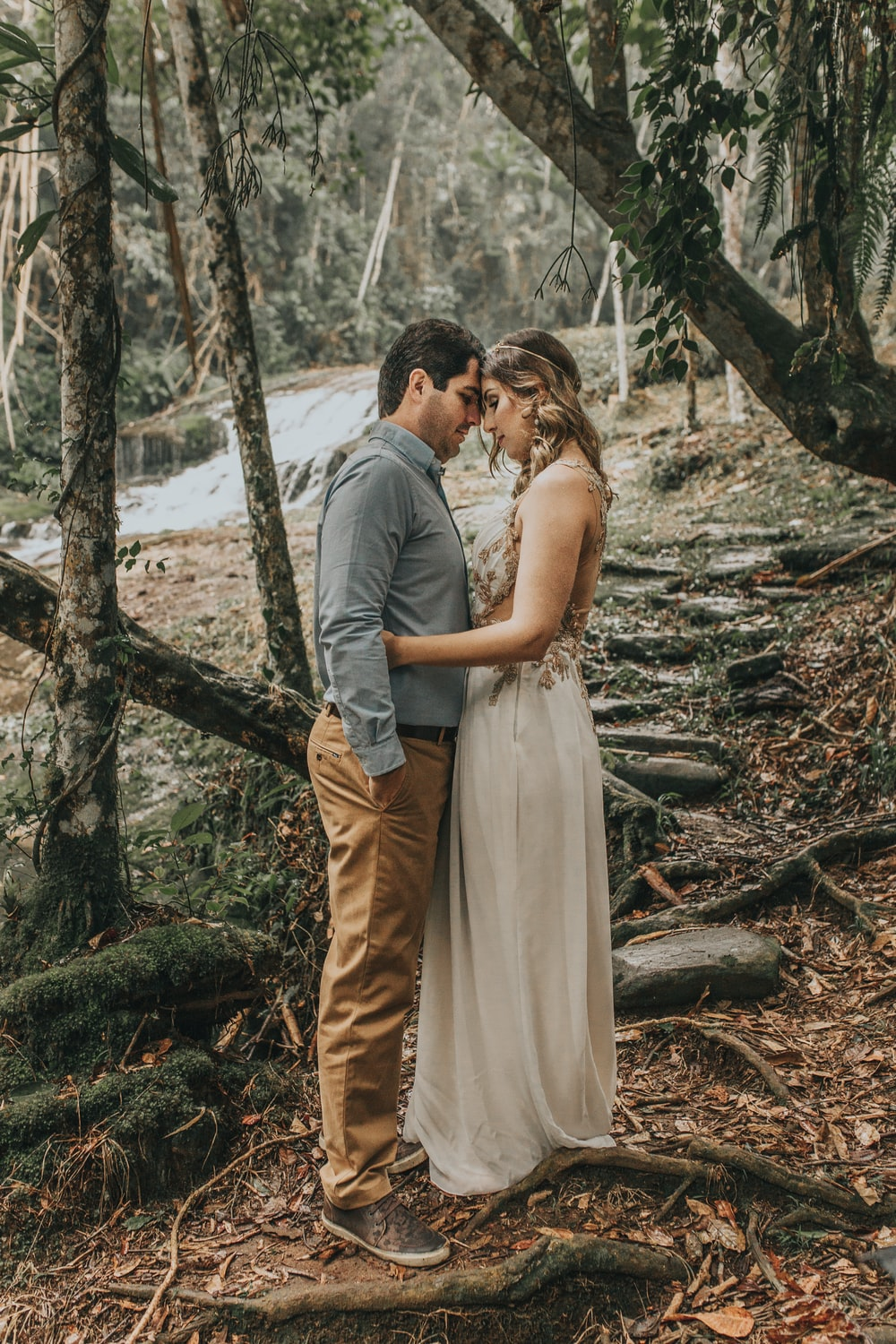 man and woman kissing near tree during daytime