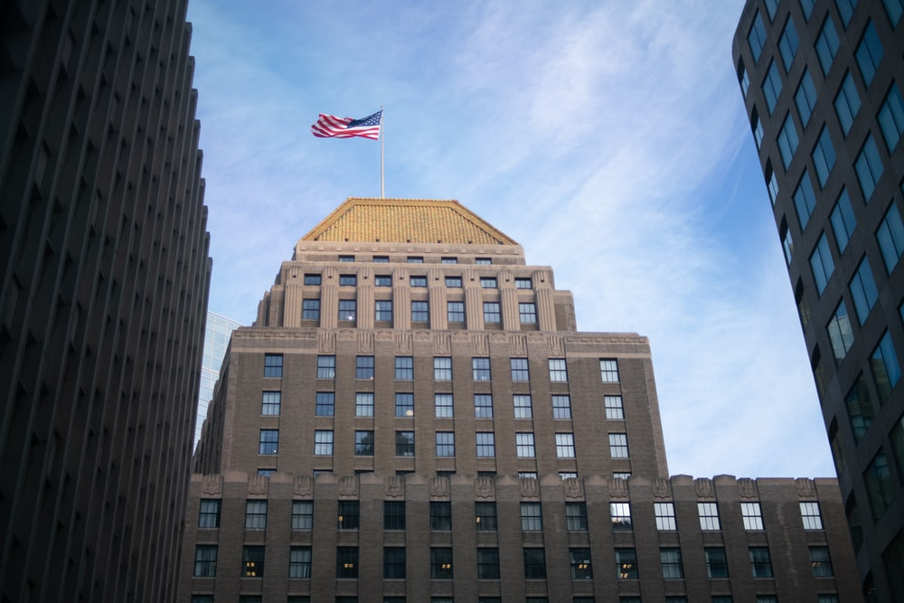 brown concrete building with flag of us a during daytime
