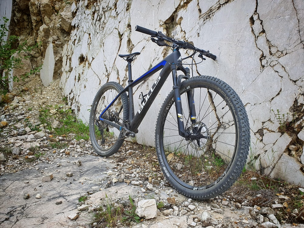 blue and black mountain bike leaning on white wall