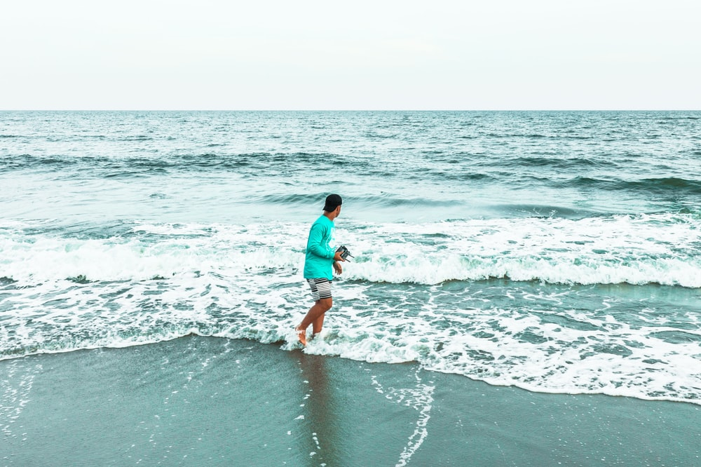 woman in blue shirt and white shorts walking on beach during daytime