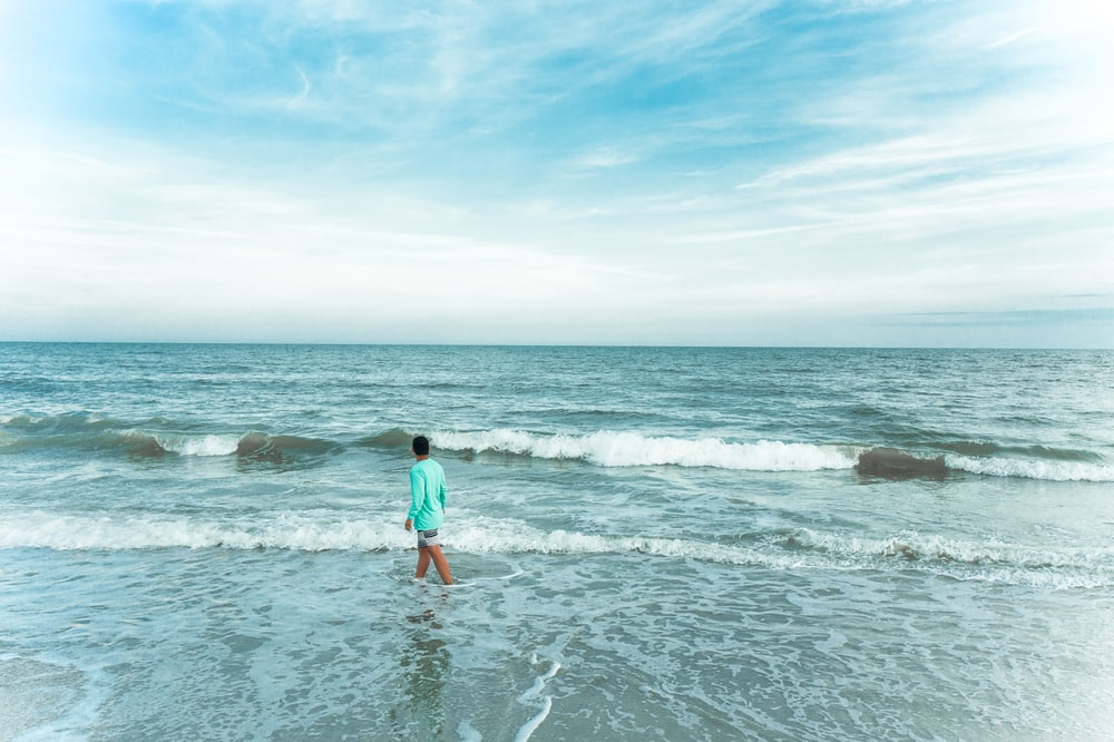 woman in blue shirt and red shorts standing on sea shore during daytime
