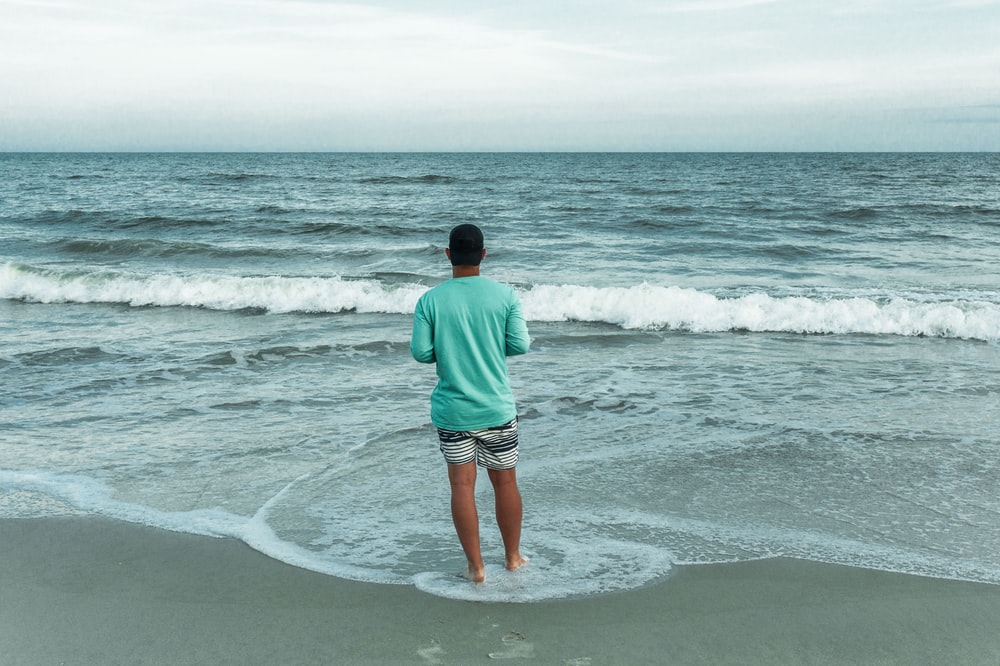 man in green shirt and brown shorts standing on seashore during daytime