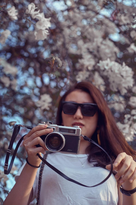 woman in black sunglasses holding camera
