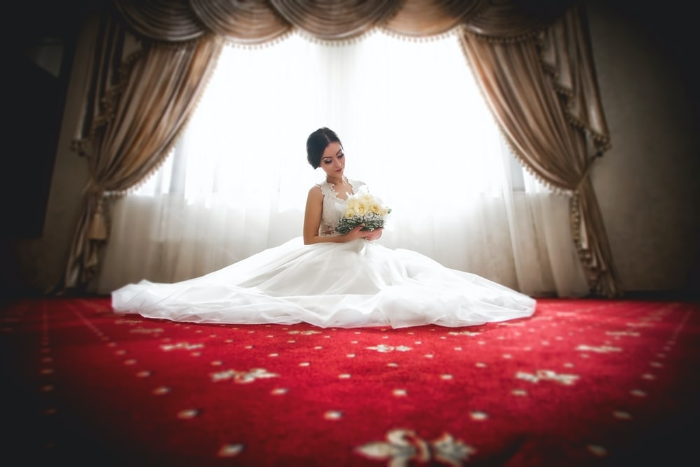 woman in white wedding gown sitting on bed