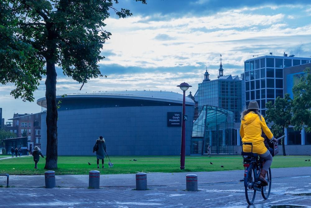 man in yellow jacket and black pants walking on sidewalk during daytime