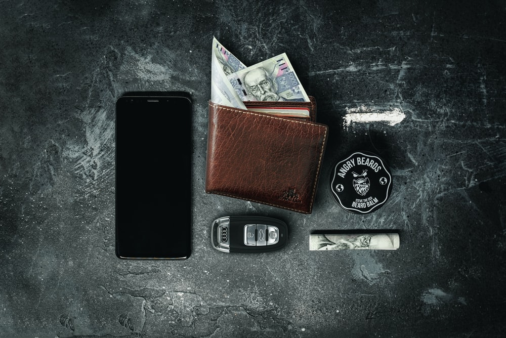 black and silver camera beside brown leather wallet