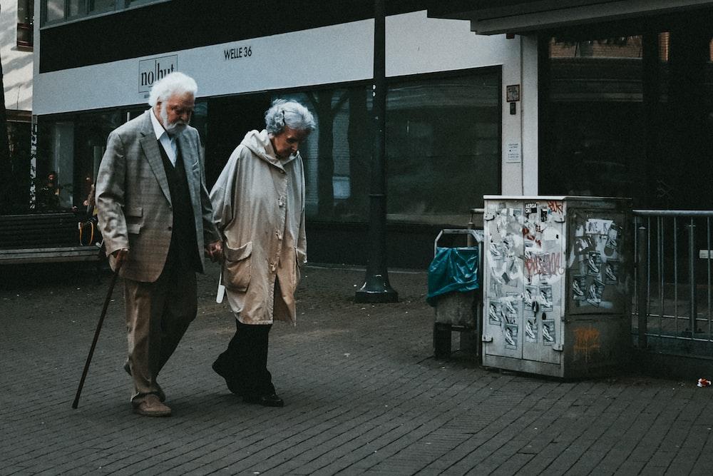 man in black suit standing beside woman in white coat