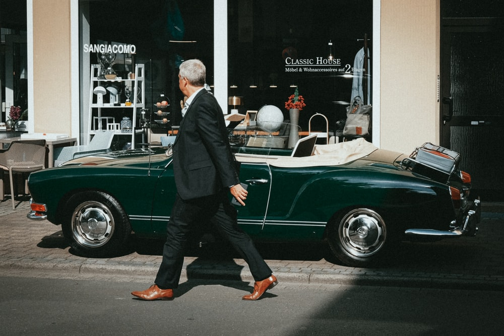 man in black suit standing beside green car