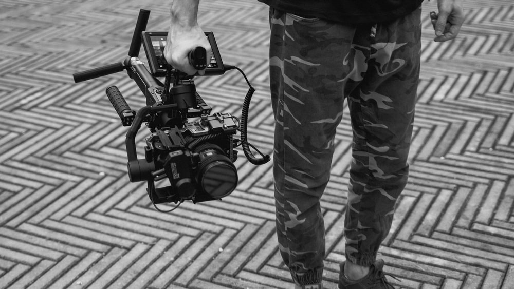 grayscale photo of man in camouflage pants holding dslr camera