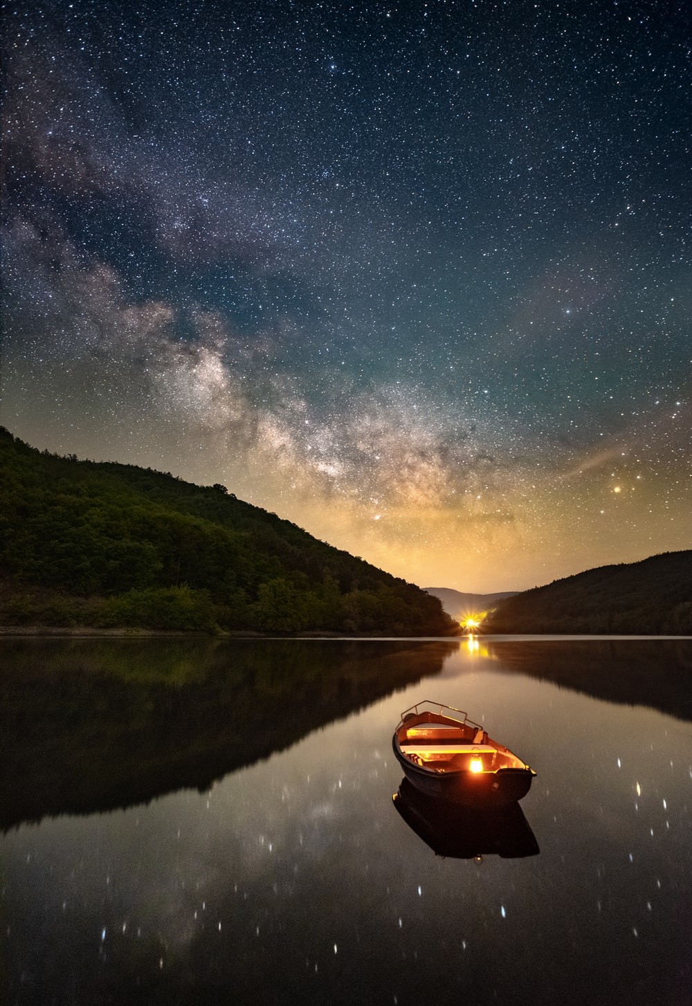 boat on lake near mountain during night time