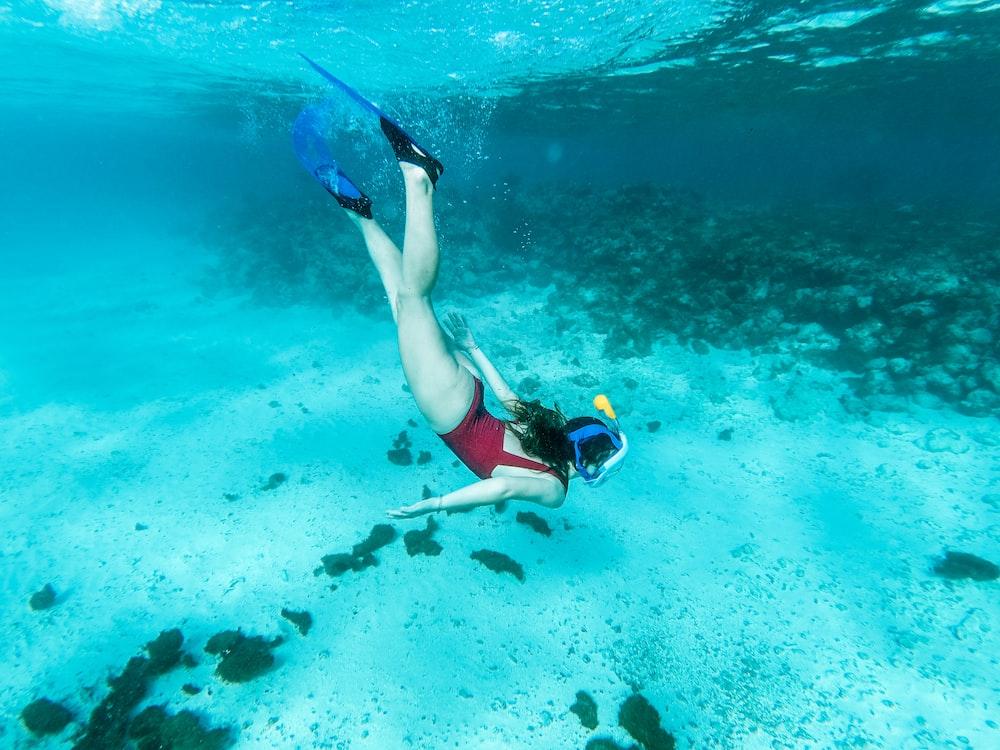 woman in blue and black bikini swimming in the sea