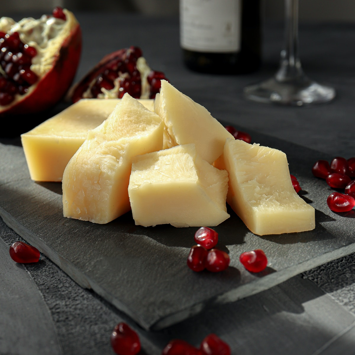 sliced cheese on black plate beside wine glass