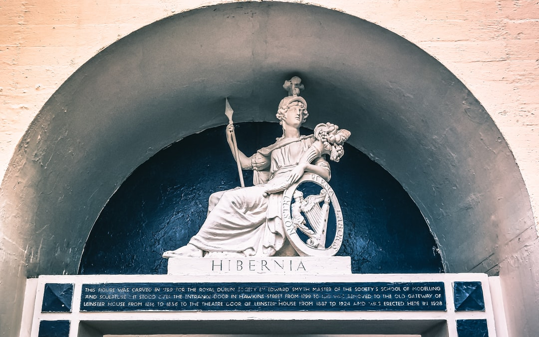 """The sculpture is of the symbol for the Royal Dublin Society. It is the Roman goddess Minerva holding a spear and a cornucopia and a shield beside her with the motto, """"Nostri plena laboris"""" (our full work) and a harp (a long-held symbol of Ireland. Beneath is """"Hibernia,"""" the classical Roman name for Ireland, and a caption which describes the sculpture as a very """"moving"""" one (Aug, 2017)."""
