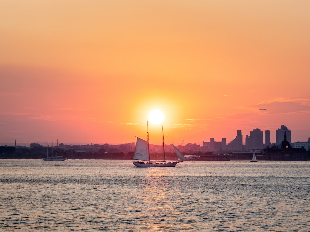 silhouette of sailboat on sea during sunset