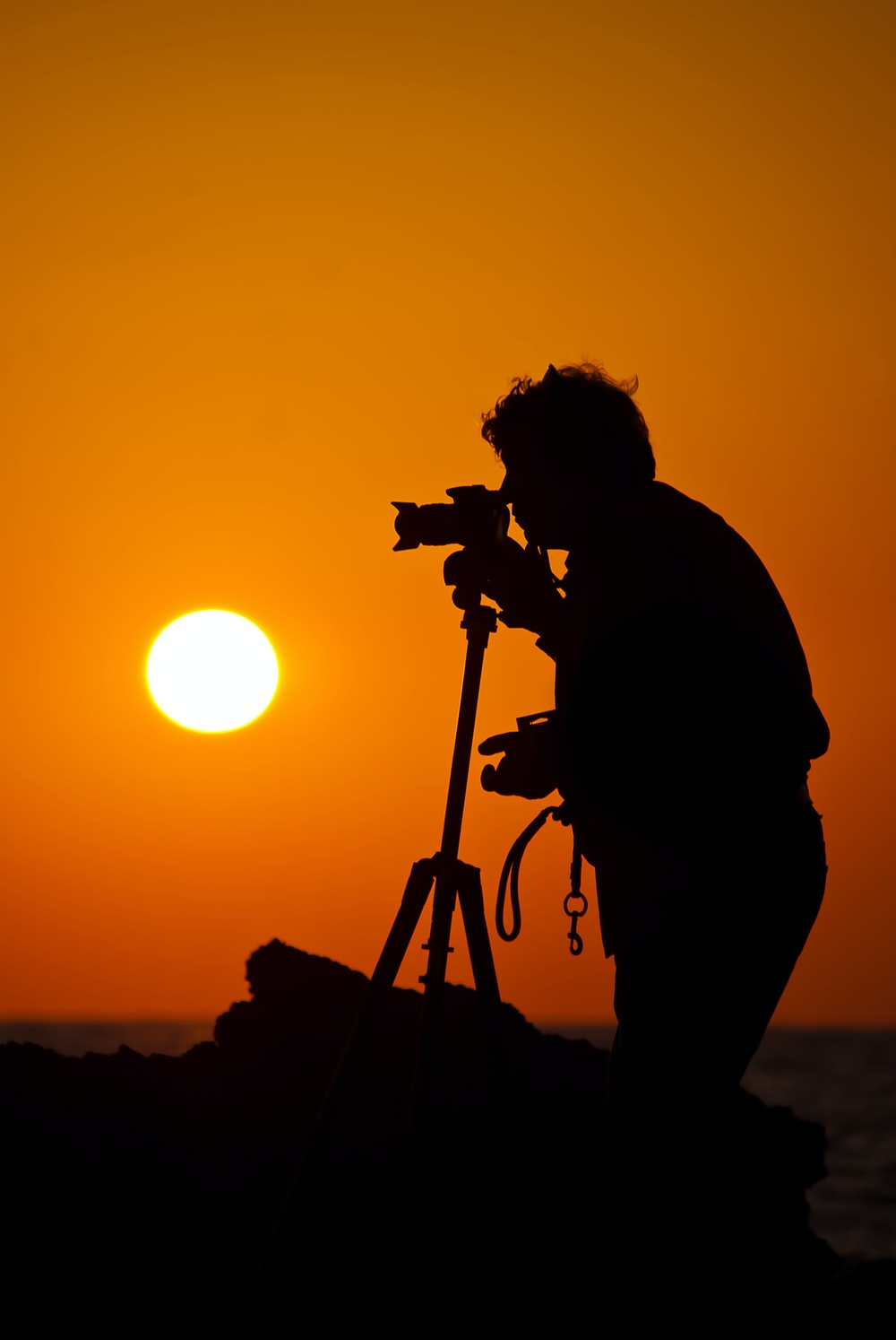 silhouette of man standing and holding camera during sunset