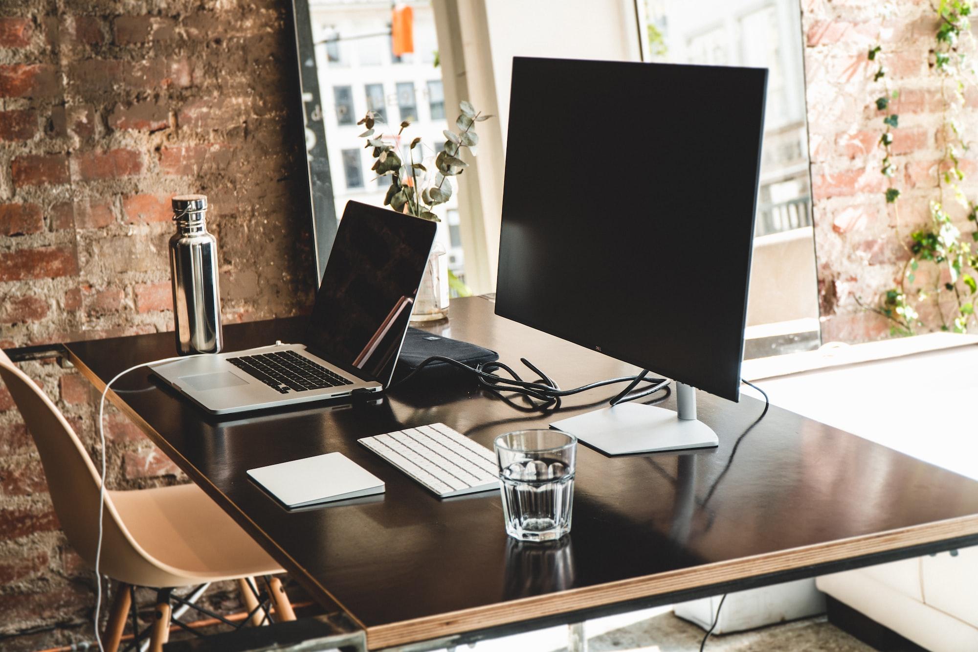 bureau rangé avec ordinateur portable, ordinateur fixe, clavier, gourde et verre d'eau  - blog.troov.com
