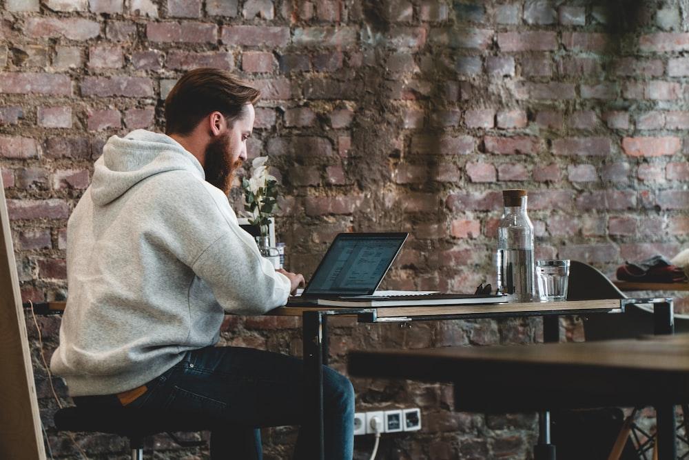 man in beige hoodie sitting on chair using laptop computer