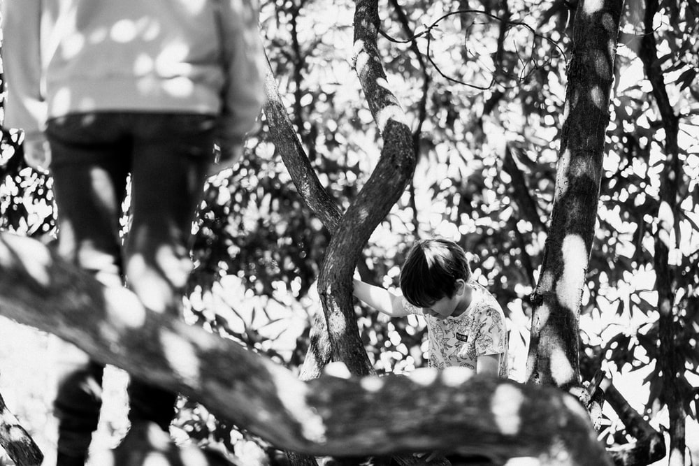 grayscale photo of girl in white shirt standing under tree