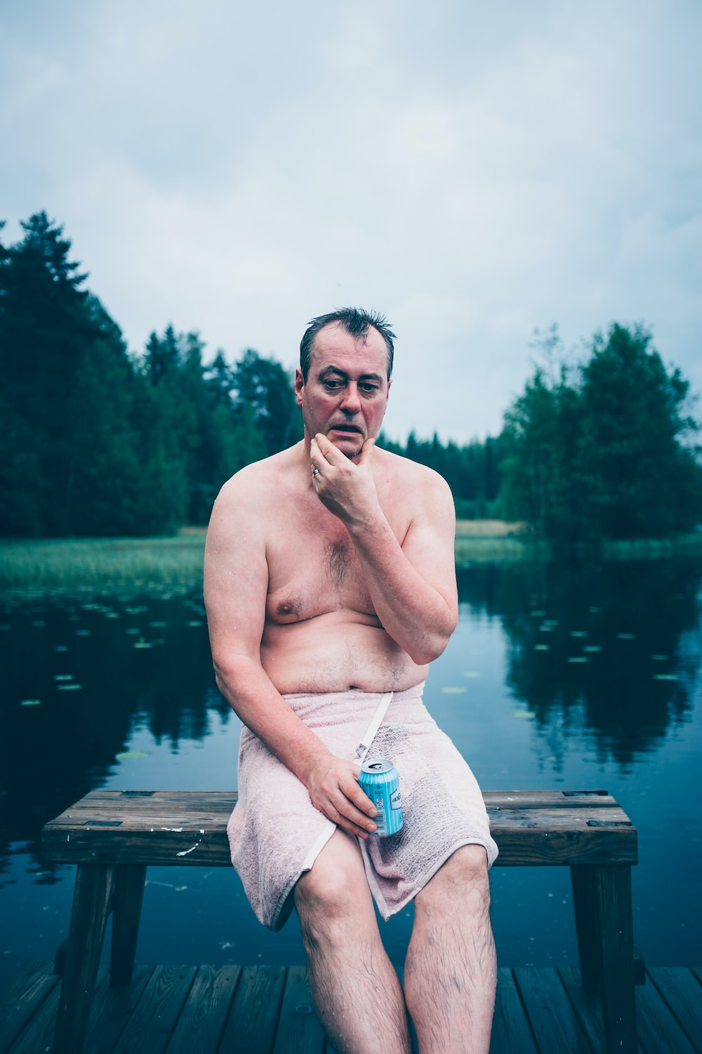 topless man sitting on brown wooden dock during daytime