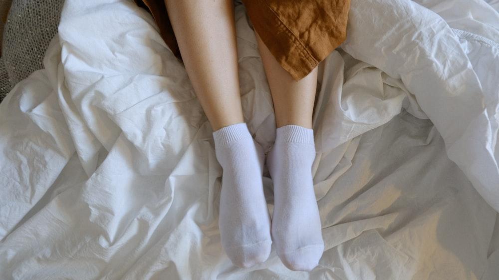 person wearing white socks on white textile