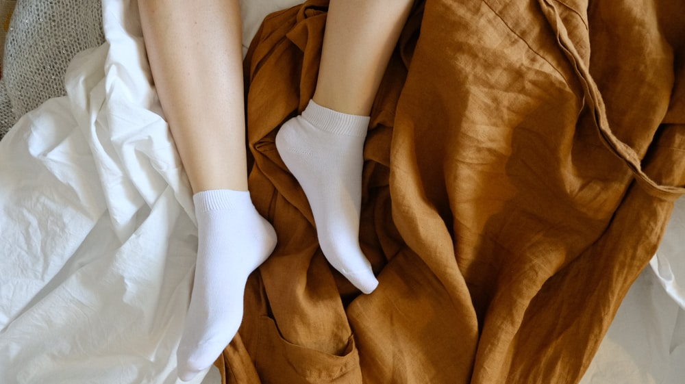 person wearing white socks on brown textile