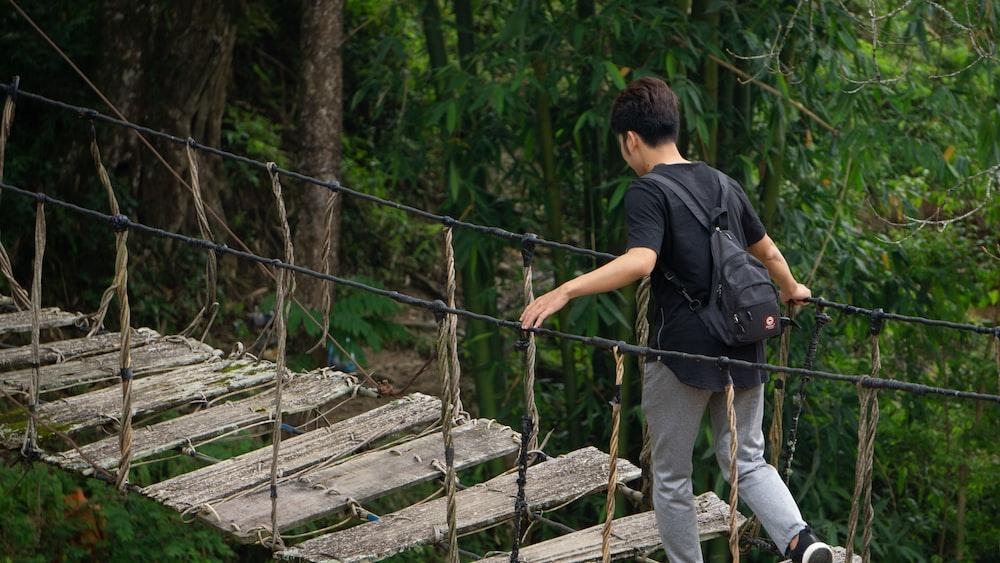man in black t-shirt and blue denim jeans walking on wooden bridge