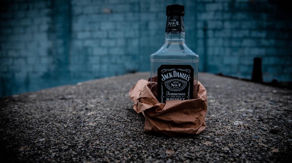 jack daniels old no 7 tennessee honey bottle beside brown paper bag on gray marble