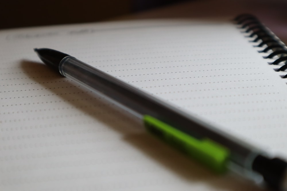 black and green click pen on white paper