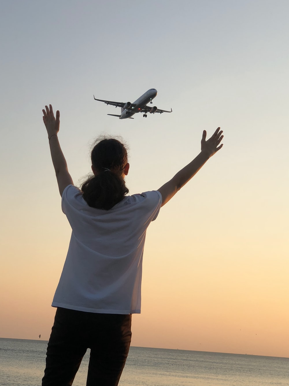 man in white shirt and black shorts holding white airplane
