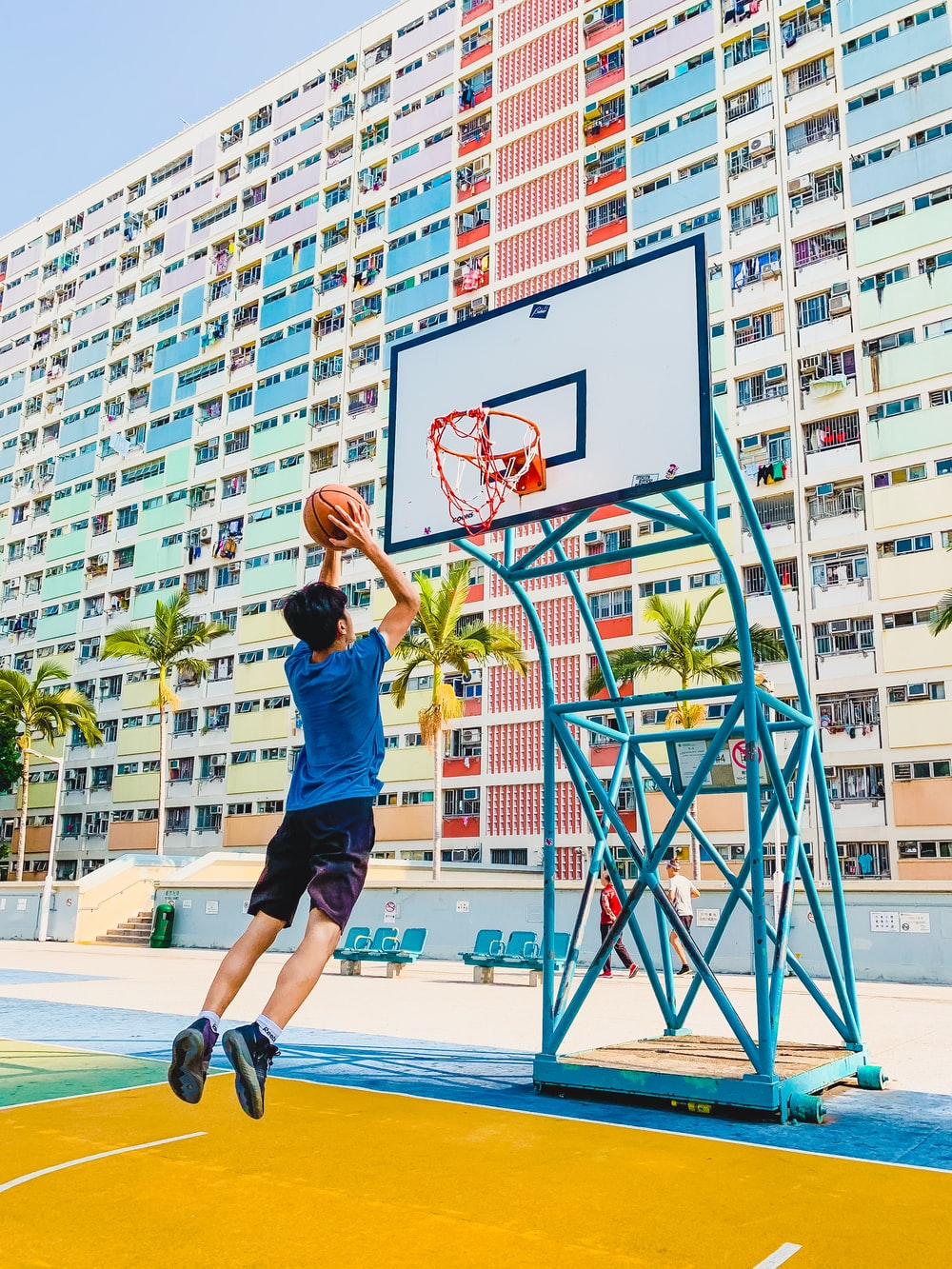 man in blue shirt and black shorts playing basketball during daytime
