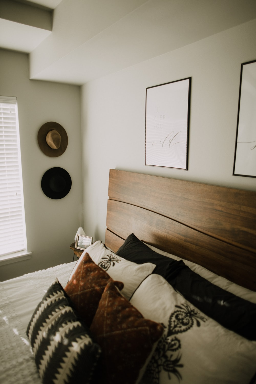 black wooden bed frame with white and black bed pillow