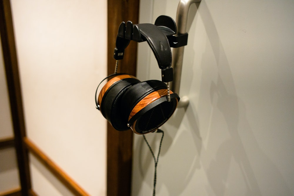 black and silver headphones hanging on white wall