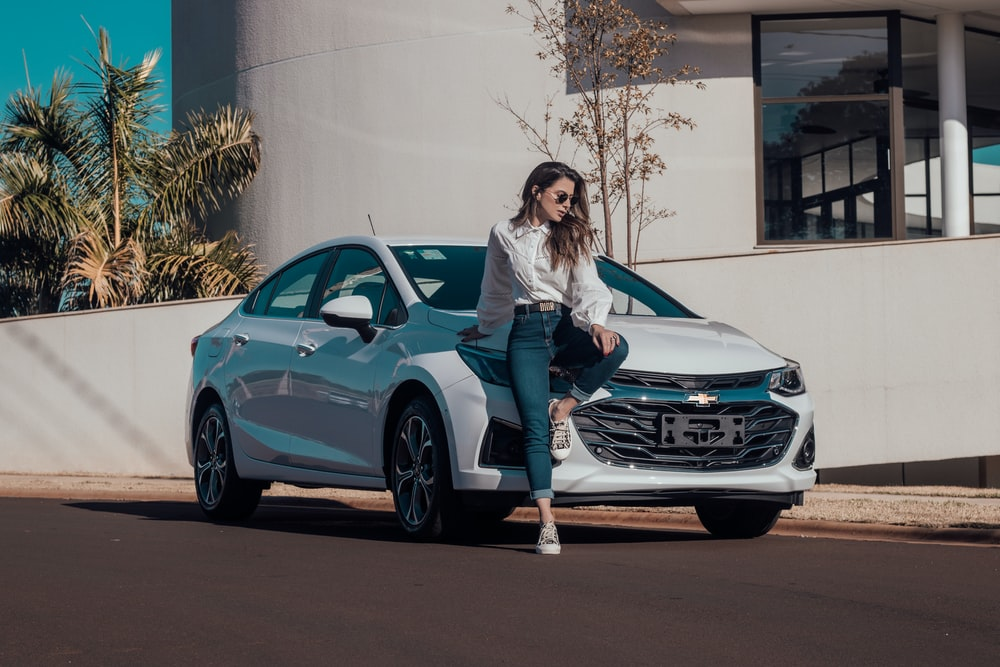 woman in white long sleeve shirt and blue denim jeans sitting on blue bmw coupe