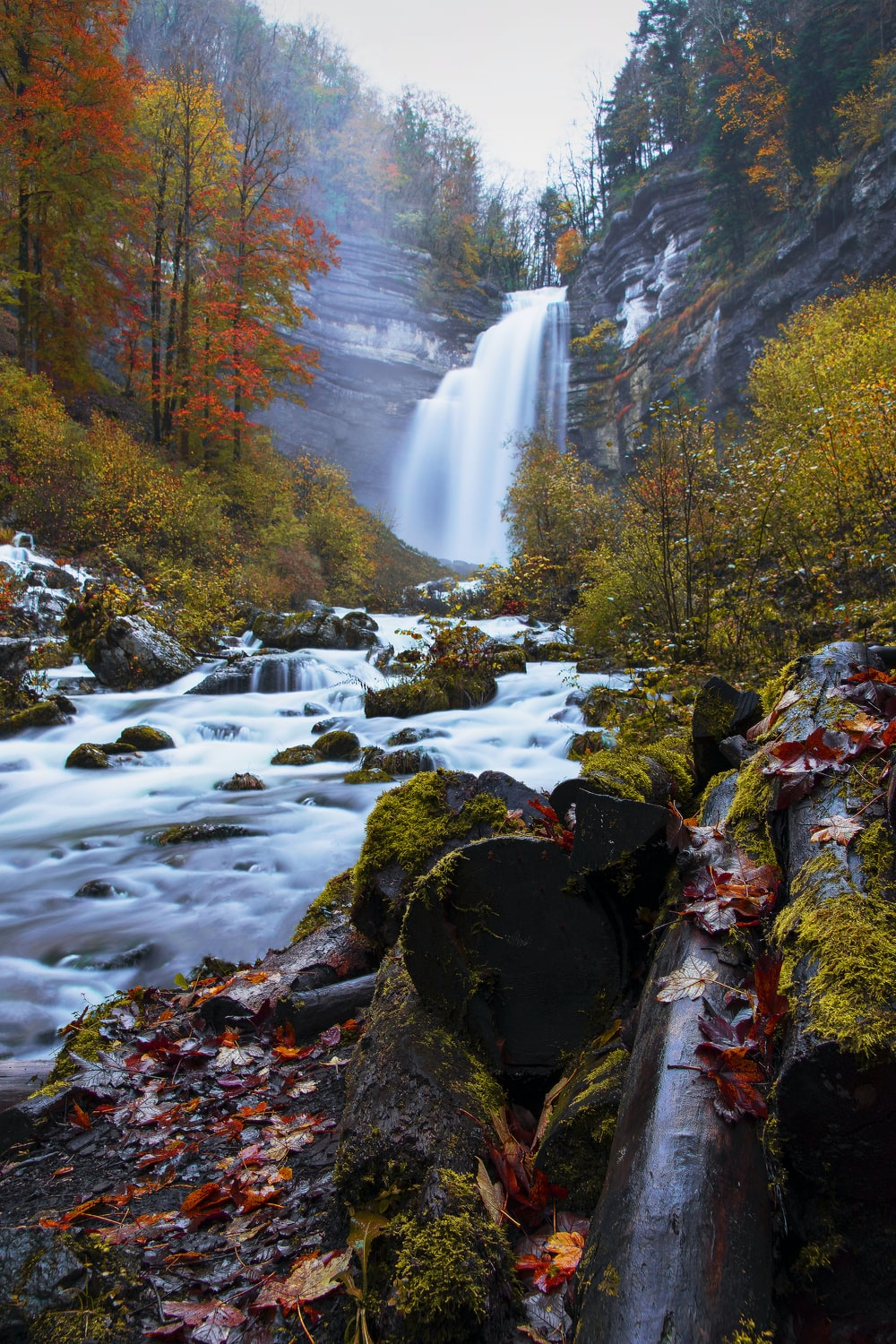 water falls on rocky mountain during daytime