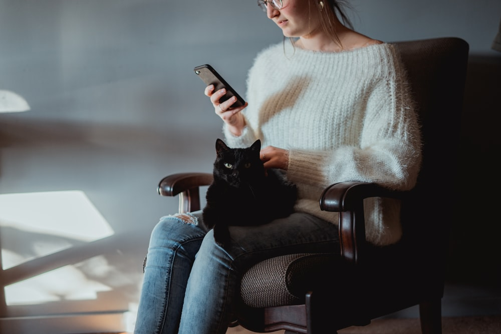 woman in white sweater and blue denim jeans sitting on black leather armchair holding silver iphone